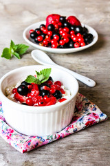 Cottage cheese with fresh berries - strawberry, red and black currant and fresh mint in a small ramekin bowl, selective focus. Organic and healthy food concept.