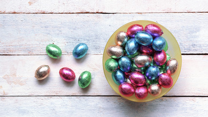 Some easter eggs in a bowl on a white wooden table. Empty copy space for Editor's text. Top view
