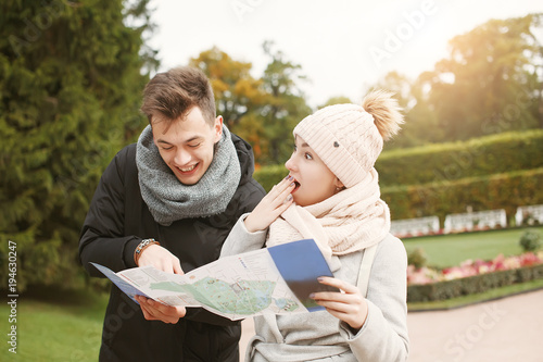 Young Guy And Girl Holding Map And Discussing Plans For