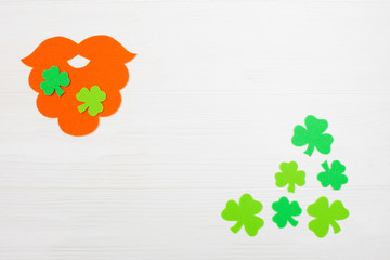 St. Patrick's Day theme colorful horizontal banner. Orange leprechaun hand made beard and green shamrock leaves on white wooden background. Felt craft elements. Copy space. For greeting card, banner