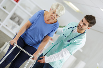 male nurse helping disabled elderly lady with a walking frame