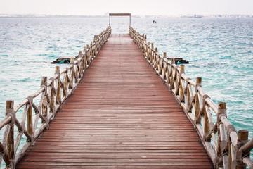 View of an empty bridge  over water.