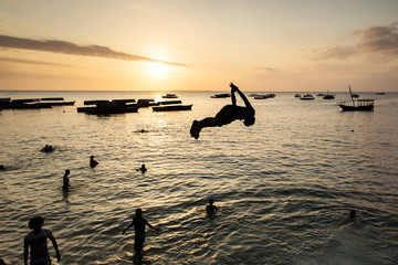 People jumping on water in Stone Town with beautiful landscape sunset in background. Zanzibar, Tanzania - Africa.