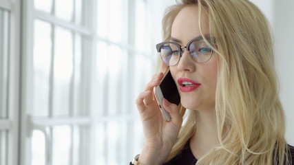 Close up of a blonde woman talking on the phone by the window.