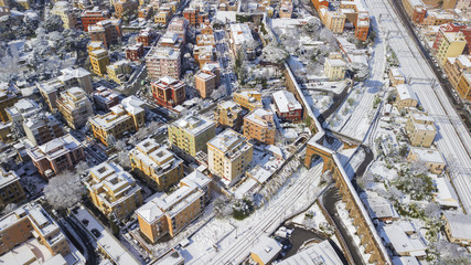 Aerial view of a group of buildings in the Tuscolana district in Rome, Italy. The buildings and streets are unusually covered with snow and ice.The roofs are passable and with antennas and TV dishes.