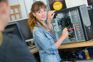 Woman repairing computer turning to speak to customer