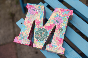 A very beautiful wooden 3d letter M on a blue wooden chair. A letter from the alphabet, the letter M