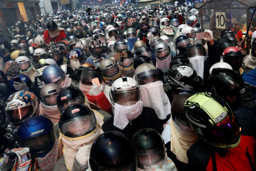 Participants wear motorcycle helmets as they attend the 'Beehive Firecrackers' festival at the Yanshui district in Tainan
