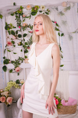 Blonde woman in short white dress presses her hands to her hips on a light background with flowers on the walls