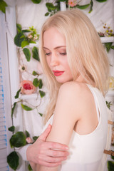 The blonde girl with a bright makeup looks down and holds her hand on her shoulder in bright interiors with flowers on the wall.