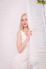 The blonde girl in a white dress and with a bright make-up peeks out from behind the white door in bright interiors