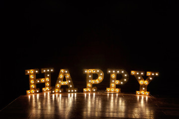 Happy letters word with glowing light retro bulbs standing on a floor