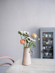 Vase mit Ranunkeln und Anemonen auf Küchentisch in Steinkrug