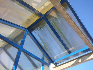 Mossy dirty glass roof of a conservatory and construction with blue frame needs cleaning