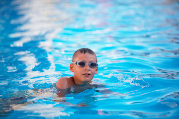 A boy is swimming and jumping in the pool