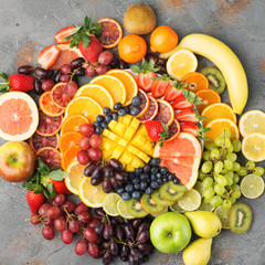 Colorful cut fruits platter in rainbow colors oranges grapes mango strawberries kiwis blueberries grapefruit on the grey concrete table arranged in circle, top view, selective focus