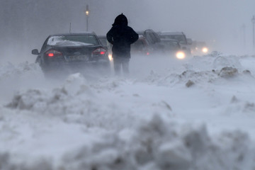 A man looks at a pile up of cars that have become stuck in heavy snow during a blizzard at night in Dublin
