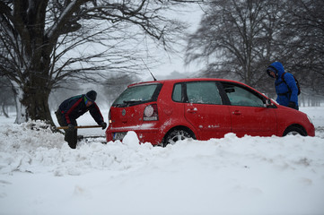 A man uses a shovel to help free a car that has become stuck in the snow in Dublin