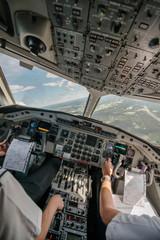 Tilt image of pilots flying airplane over landscape