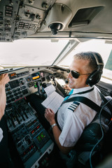 Confident smiling pilot with documents sitting in cockpit