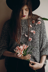 stylish hipster girl in hat holding pink flowers and petals on sweater growing. boho woman with beautiful alstroemeria in hands. creative sensual female  portrait. eco concept. save and protect