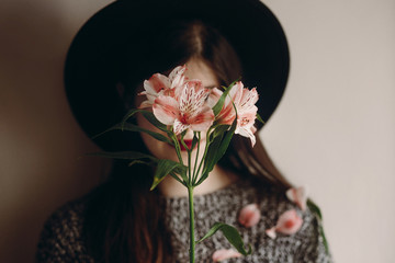 stylish hipster girl in hat holding pink flowers and petals on sweater growing. boho woman with beautiful alstroemeria in hands. focus on flower. eco concept. save and protect