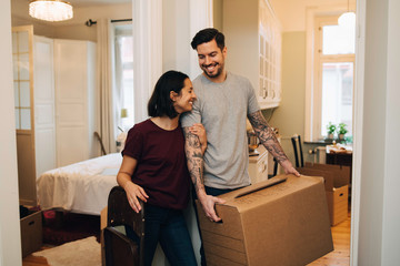 Cheerful woman standing with man carrying box at home