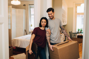 Portrait of woman standing with smiling man carrying box at home