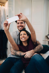 Smiling couple taking selfie on mobile phone while resting on bed in bedroom