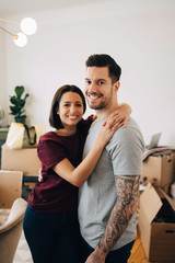 Portrait of smiling couple embracing while standing in living room during relocation