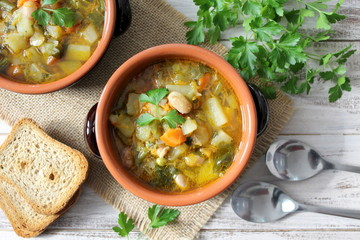 Vegetables soup on the wooden background. Vegetarian and vegan food. Top view.