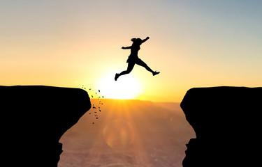 Frau spring über Abgrund vor Sonnenuntergang.