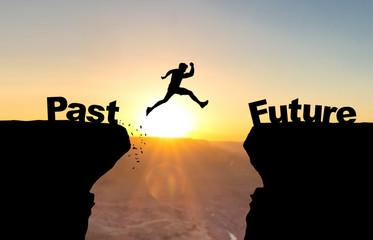 Mann spring über Abgrund vor Sonnenuntergang mit Beschriftung Past/Future. Wall mural