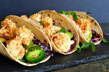 Roasted coconut cauliflower tacos. Healthy, vegan meal. Close up, side view on a dark background.
