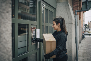 Female messenger ringing intercom on closed door while carrying box on sidewalk