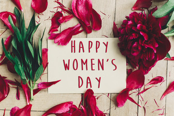happy women's day text sign on craft card and beautiful red peonies on wooden rustic background, flat lay. modern greeting card. womens day
