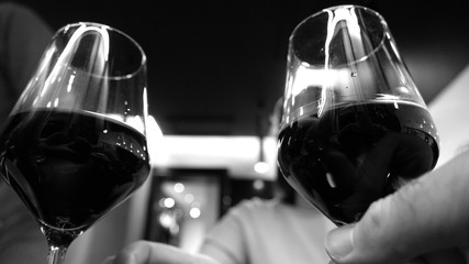 Elegant woman drinking red wine in luxury resaurant celebrating birthday or dating with her male friend black and white