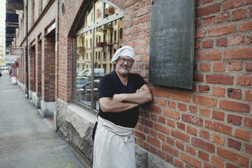 Portrait of senior male baker leaning on brick wall outside bakery