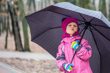 Little  girl walking under umbrella in a city park