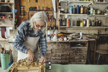 Woman restoring gilded frame in workshop