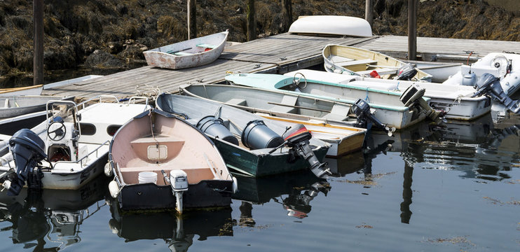 Small boats tied to dock and each other in Maine