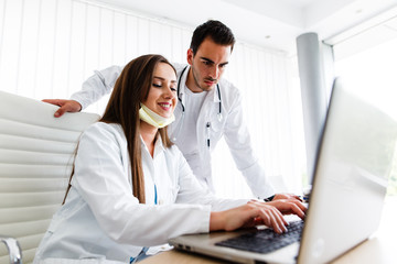 Beautiful nurse and young doctor works on laptop