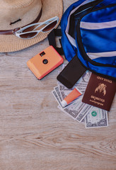 Top view accessories for travel on old wood, Shells, yellow camera, smartphone,glasses, Sunscreen,hat, Target and Dollar on Thailand passport. photo concept travel and life style.