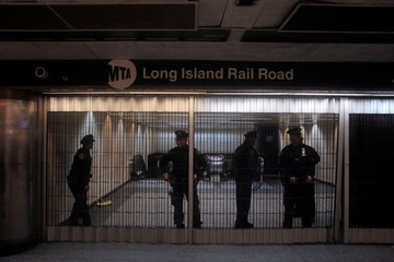 Members of the Metropolitan Transport Authority Police stand behind a closed entrance at Pennsylvania (Penn.) Station following multiple delays on the Long Island Rail Road service during a winter nor'easter in New York