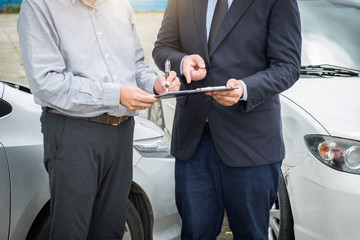 Insurance Agent examine Damaged Car and customer filing signature on Report Claim Form process after accident, Traffic Accident and insurance concept
