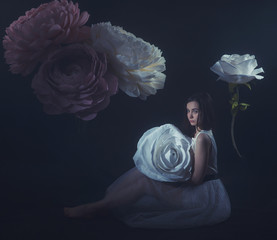 girl in a light dress among the huge flowers made of paper and formina