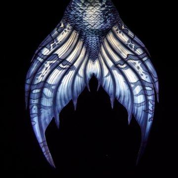 Mermaid tail fluke, blue, on black background, underwater