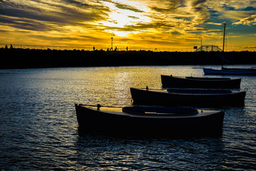 Small boats in silhouette are anchored at St Kilda Marina in front of the penguin scantuary in Melbourne Australia
