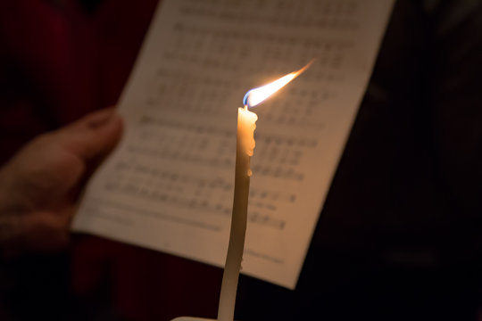 Single candle against sheet music