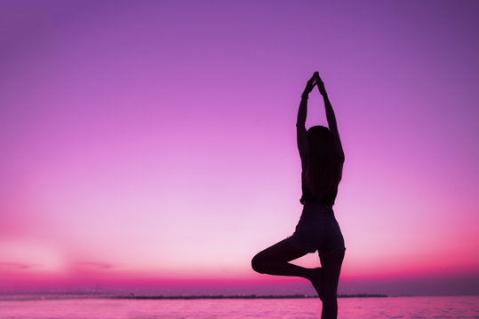 Silhouette of woman practice yoga on beach of sunset background